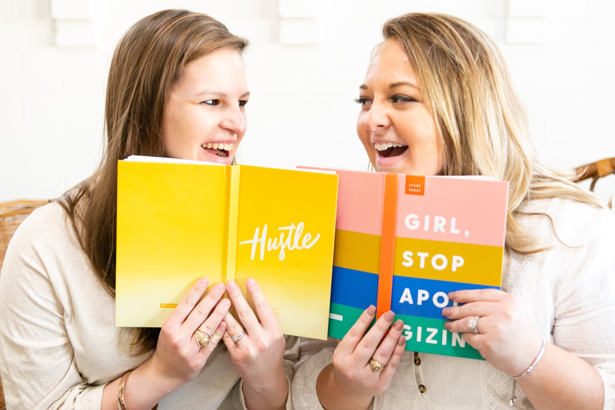 Creative entrepreneurs smiling with books by Paty Araujo Photography